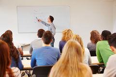 students-listening-to-teacher-class-whiteboard-30013227